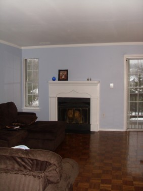 blue living room, white fireplace, brown couch, parkay floors